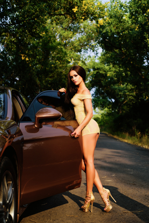 Erotic perfect female body dressing in golden colors. Long legs near luxury car. Frank mens dream of an ideal wife.
