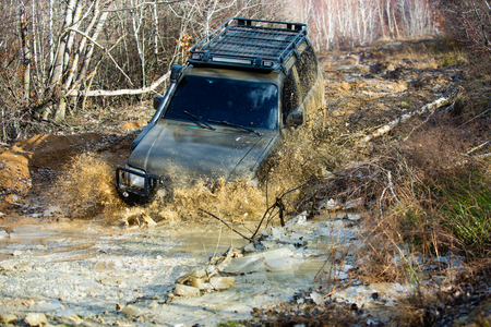 Extreme weekends. A car during a tough off-road competition diving in a muddy pool. Driver competing.