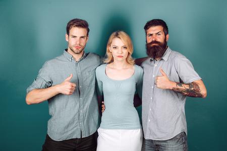 Liebesdreieck-Konzept. Blondes Mädchen und zwei Jungs in Freizeitkleidung in die Kamera blicken. Standard-Bild