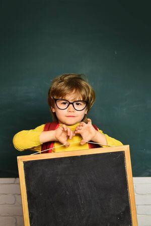 Back to school - education concet. Cute little preschool kid boy in a classroom. School kids against green blackboard.