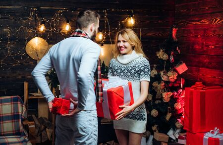 Christmas couple in love. Mutual new-year-gifts. Beloved is hiding a present behind back. The girl is holding a large red box in her hands. Stockfoto - 124924478