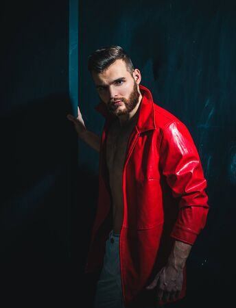 Portrait Of Young Handsome Man. Handsome man wearing red leather jacket on naked muscular torso on dark background, looking on camera.