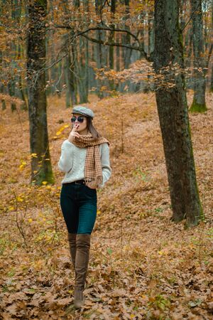 Autumn woman, Brunette girl is smoking a cigarette in the park during autumn. Fashionable model wearing warm brown boots and cap in the forest. Resting from noisy city concept.