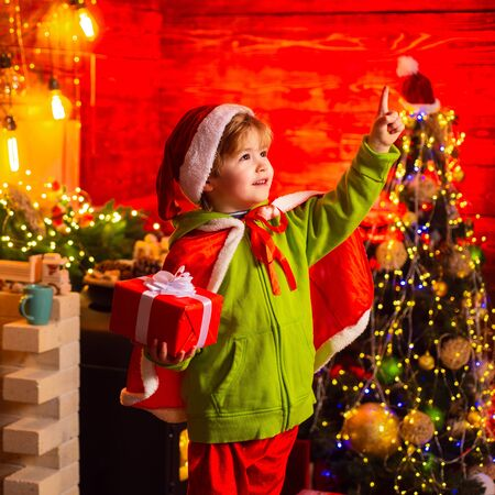 Cute boy shows a finger on the Christmas light. Santa Claus Workshop. Stockfoto