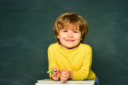 School or college pupil showing parents a test with good grade. School children. Cute boy with happy face expression near desk with school supplies