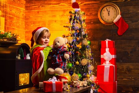 Merry Christmas and Happy New year. Handsome boy is playing with Christmas gift in bright clothes. Natural wooden and textile toys for childrens play.