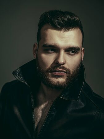 Portrait of stylish handsome young man. Old-fashioned clothing, retro style leather jacket. Masculinity concept. Brutal bearded biker with hairstyle. Attractive male.