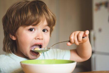 Hungry little boy eating. Cheerful baby child eats food itself with spoon. Tasty kids breakfast. Baby eating food on kitchen. Happy baby boy eats healthy food spoon itself.