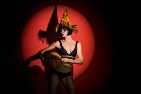 Halloween sexy concept. Erotic girl in black lingerie with a witch hat. Holding the yellow pumpkin. Halloween party for adults. Stock Photo