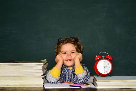 September 1. Blackboard copy space. Back to school. Funny little boy pointing up on blackboard. Great study achievement.