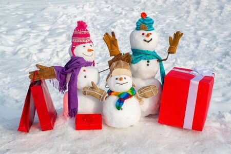 Snowman with shopping bag and gift on the white snow background. Funny snowman in stylish hat and scarf on snowy field. Cute snowman in hat and scarf on snowy field with surprise Christmas gift.