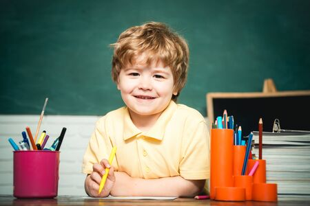 Home or school education. Portrait child from elementary school. Boy pupil from elementary school at the school yard. Cheerful smiling child at the blackboard. Banco de Imagens
