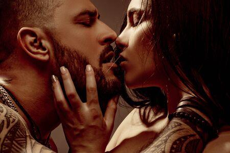接吻。恋にカップルの肖像画をクローズアップはキスしています。本当のロマンチックな情熱的な瞬間。美しいガールフレンドを抱き合う入れ墨を持つひげを生やした男。カップルの感情的。