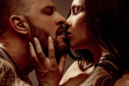 Kiss. Close up portrait of couple in love is kissing. Real romantic passionate moment. Bearded man with tattoo clasping beautiful girlfriend. Emotive of sexy couple.