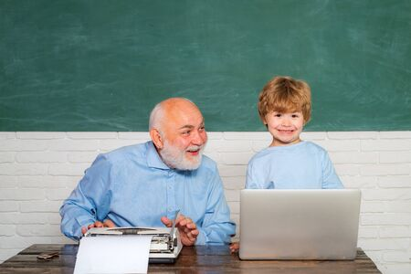 Happy Pupil with over blackboard background. Elementary school teacher and student in classroom. Father teaching her son in classroom at school. Concept of a retirement age. Imagens - 124924597