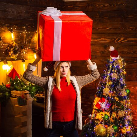Girl with christmas gift box. Girl with christmas hat and many gifts celebrating the christmas holidays having big box. A puzzled and disappointed face.