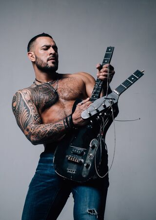 Music shop. Learning and Playing Music for Adults. Music and Dj concept. Stylish brutal man with a beard, a tattoo is imitating a game on the guitar. Concentrated unshaven man. Sexy look of a male mod
