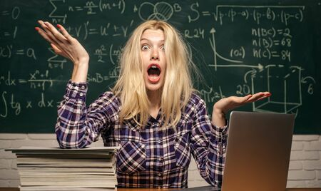 Negative human emotions face expression feeling life perception. Student tired of studying in classroom. Back to school. Bored student doing homework on line with a laptop.
