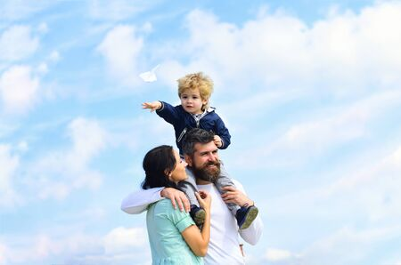 Father mother and son in the park. Freedom to Dream - Joyful Boy Playing With Paper Airplane. Family Time. Parenting. Happy father giving son back ride on sky in summer. Stock Photo