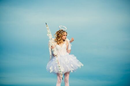 Une belle adolescente aux cheveux blonds bouclés et un arc et des flèches comme Cupidon - Saint Valentin. Petit ange amoureux. Espace pour le texte. Portrait d'une petite fille Cupidon
