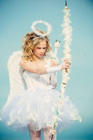 El pequeño Cupido lindo dispara un arco. Retrato de una niña cupido. Bonita niña blanca como el Cupido con un arco y una flecha felicitando el día de San Valentín. Postal para el día de San Valentín