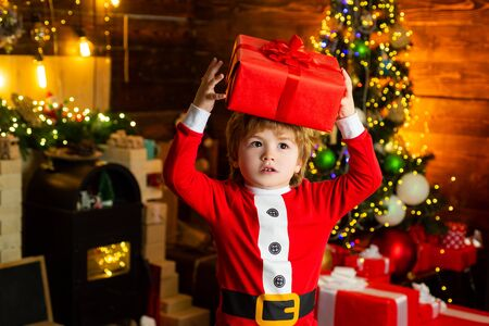 Happy child with christmas gift box. Blonde boy holding a red box over his head. Interested and puzzled face. Stockfoto