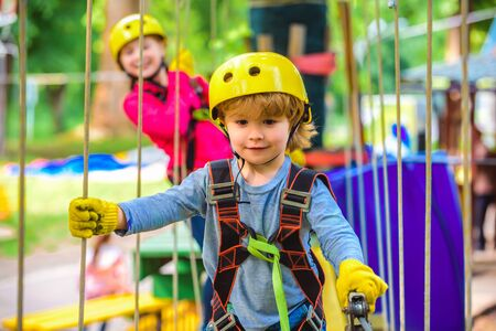 Happy little boyn calling while climbing high tree and ropes. Eco Resort Activities. Go Ape Adventure. Roping park. Toddler age. Hiking in the rope park boy in safety equipment.