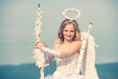 Innocent Girl with angel wings standing with bow and arrow against blue sky and white clouds. St Valentines day. Little angel girl against sunny sky