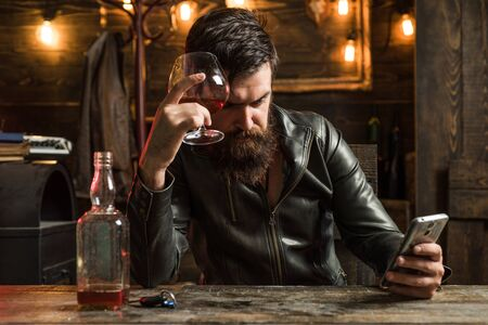 Drinking and party concept. Man drinks brandy or whiskey. Bearded man wearing suit and drinking whiskey brandy or cognac. Sommelier tastes alcohol drink. Degustation and tasting.