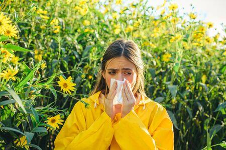 Fioritura del topinambur. Tovagliolo per naso che cola. Donna che indossa giacca gialla. Allergia ai pollini, ragazza che starnutisce in un campo di fiori.