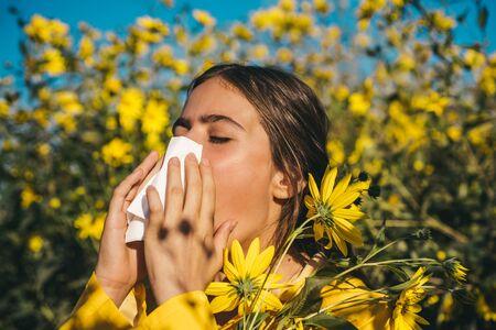 Pollen allergy, girl sneezing in a field of flowers. Jerusalem artichoke flowering. Napkin for running nose. Woman wearing yellow jacket.