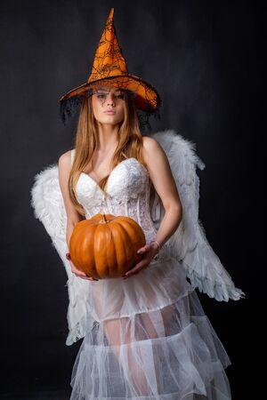 Happy gothic young woman in angel Halloween costume. Angel Fashion Art design scene. Halloween girl in costume angel on black background. Beauty Halloween teen.