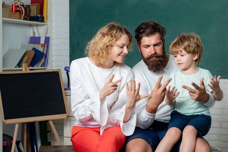 Parents encouraging their little son before the first day of school. Young happy family schooling math together. Family school partnerships examples. Stock Photo