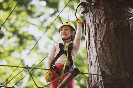Little girl having fun at adventure park. Artworks depict games at eco resort which includes flying fox or spider net. Adventure climbing high wire park. Child.