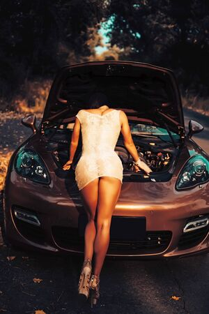 Sexy brunette girl stand by the broken car in short dress and doesnt know what to do. Rear view.