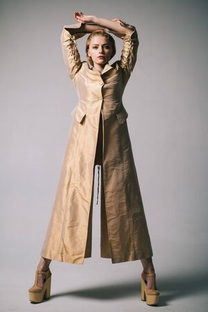 Full-length studio fashion portrait of young beautiful model wearing long white trench coat, golden heels, posing on grey background.
