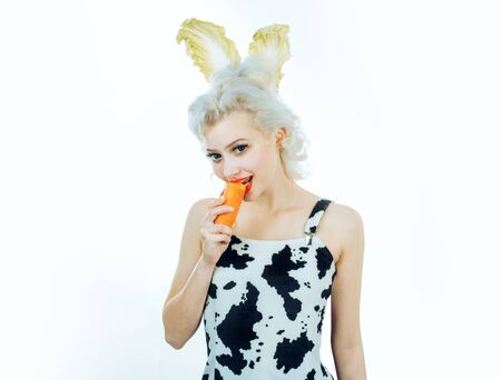 Close-up portrait woman dressing in a bunny costume, eating carrot.