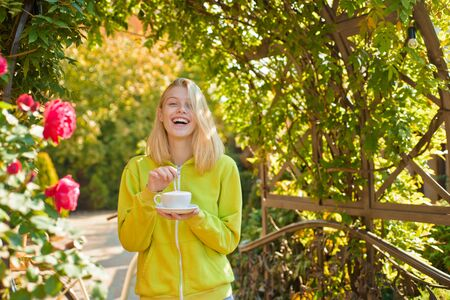 Autumn coffee. Smiling girl with a white cup of fragrant coffee, a blonde in a sweater and a cup of cappuccino. Carefree young woman in trendy vintage pullover or sweater enjoying weather.