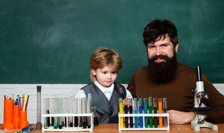 Happy little scientist making experiment with test tube. Young boy doing his school homework with his father. Home schooling. Chemistry the Science Classroom Stock Photo