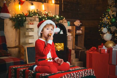 Christmas kids. Merry Christmas and Happy Holidays. The boy is sitting on the table and eating a croissant. Little boy wearing a carnival costume Santa Claus against the background of holiday decorations.