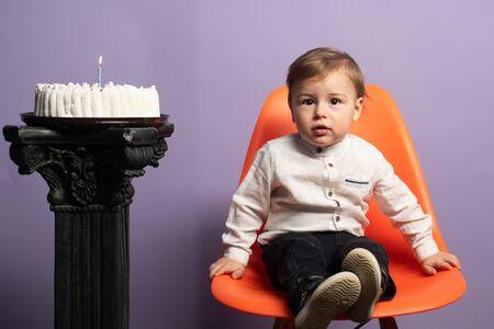 First celebration birthday. Birthday boy sitting on the chair near the cake.