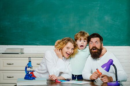 Learning and education concept. Happy family. Mother father and son together schooling. Boy from elementary school. Stock Photo