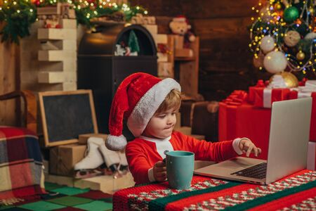Merry Christmas and Happy New year. Young Santa Claus is using a laptop at his workshop. Christmas gifts with e-commerce. Stockfoto - 124924901