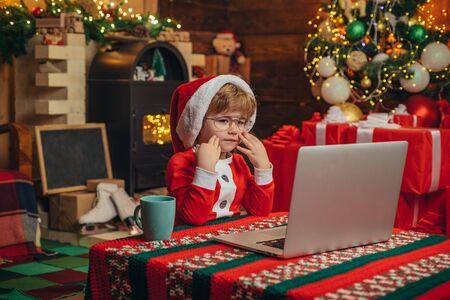 Christmas gifts with e-commerce. Open-ended Games. Young Santa Claus is using a laptop at his workshop. Merry Christmas and Happy New year. Stockfoto