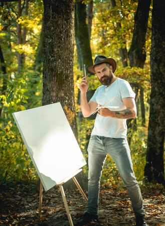 Hipster artist in a hat creating art in the woods. Art concept. Painting in nature. Start new picture. Painter with easel and canvas. Stock Photo