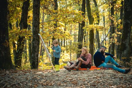Autumn family outdoor. Busy family in autumn park, spending time together but separately, losing communication. Contemporary values. Dependency on gadgets. Banco de Imagens - 124924928