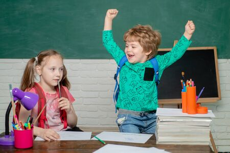Back to school - education concept. Happy cute clever boy and cute little girl with book. Cheerful smiling little boy and cute little girl having fun against blackboard - school concept.