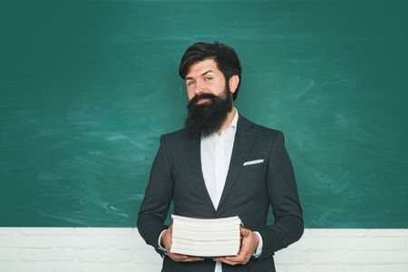 Portrait of male University Student indoors. Student and tutoring education concept. Learning and education concept. Exam in college. Bearded professor at school lesson at desks in classroom.