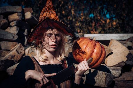 Halloween woman. Scary bloody girl in wizard orange hat with pumpkin. Woman with red blood and with blond hair. Halloween party art design. Set of funny Halloween elements. Fearlessness concept. 免版税图像