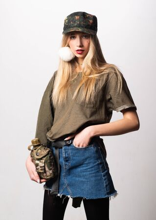 Magnificent white girl in military clothes posing with flask. Studio portrait of beautiful lady in jeans skirt looking on photographer.